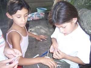 Girls in Nicaragua making beads out of old magazines.