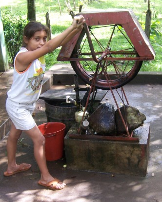Girl getting water from a well